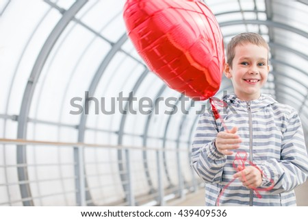 joyful boy with red balloon heart in hands. Child smiling happily holding a red heart. the concept of happiness in love. copy space for your text - stock photo