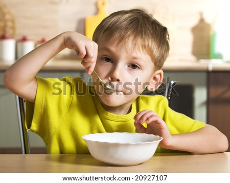Joyful breakfast of little boy - stock photo