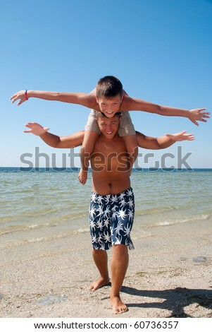 Joyful brothers having fun at the beach - stock photo