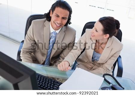 Joyful business team using a computer in an office - stock photo