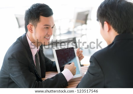 Joyful businessman presenting optimal business solutions to his partner - stock photo