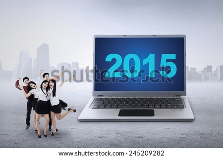 Joyful businesspeople expressing happy with number 2015 on a big laptop computer, shot outdoors - stock photo