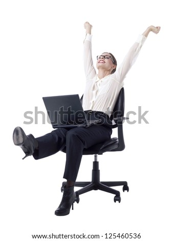 Joyful businesswoman raising her fists in the air while sitting on an office chair