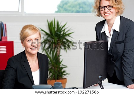 Joyful businesswomen enjoying at work desk - stock photo