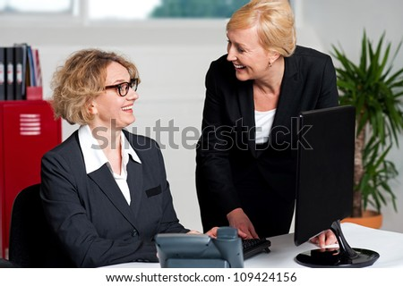 Joyful businesswomen enjoying at work desk during office hours - stock photo