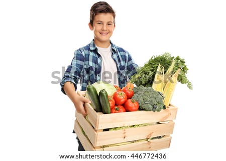 Joyful child carrying a wooden crate full of fresh vegetables isolated on white background - stock photo