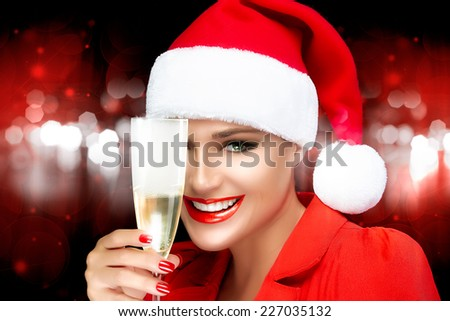 Joyful Christmas girl in Santa hat with a beautiful big smile and champagne glass. Festive makeup and manicure. Christmas greetings. Fashion portrait over background of red and white sparkling lights - stock photo
