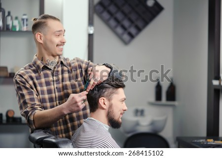 Joyful conversation. Cheerful skillful barber making a haircut with scissors to a young bearded man - stock photo