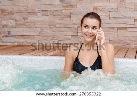 Joyful conversation. Young smiling woman talking over the phone bathing in jacuzzi in a spa center - stock photo