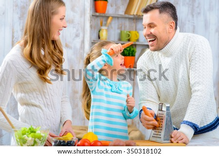 Joyful cooking. Cheerful delighted smiling family making salad and having fun while cooking - stock photo