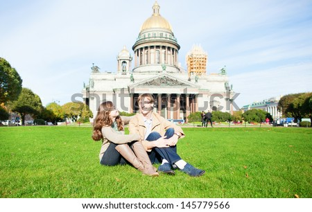 Joyful couple sitting on the grass near St. Isaac's cathedral - stock photo