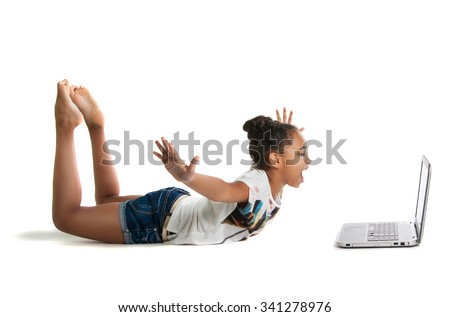 Joyful dark-skinned teen girl with a laptop. Girl shows his delight - stock photo