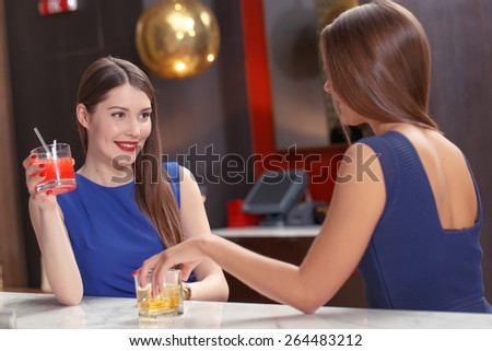 Joyful evening with a friend. Two beautiful young women wearing dresses having a drink in a bar
