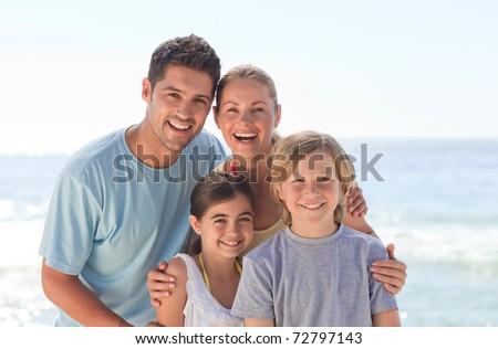 Joyful family at the beach - stock photo