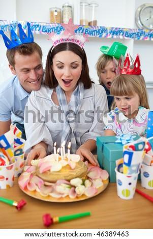 Joyful family celebrating mother's birthday in the kitchen - stock photo