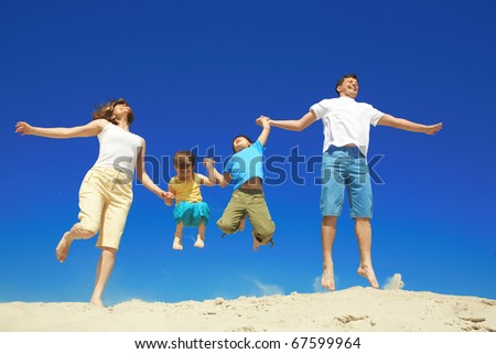 Joyful family jumping together during vacation - stock photo