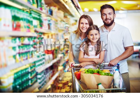 Joyful family of father, mother and daughter looking at camera in supermarket - stock photo