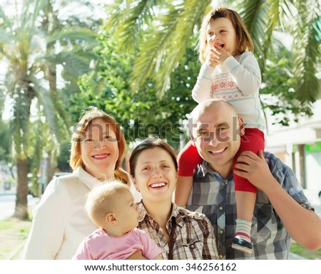 joyful family of four with grandmother enjoying time at city street in summer
