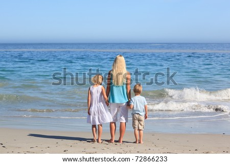 Joyful family walking on the beach