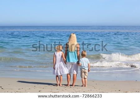 Joyful family walking on the beach - stock photo