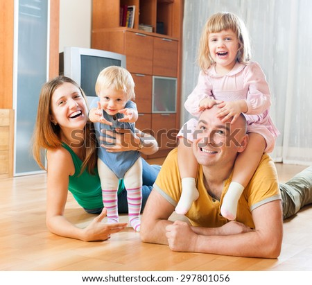 Joyful family with two children in home interior - stock photo