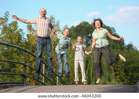 joyful family with two children is jumping on a bridge. family is handies. - stock photo