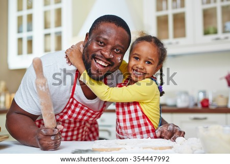 Joyful father and daughter cooking homemade pastry - stock photo