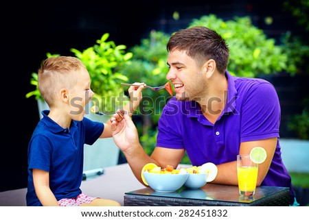 joyful father and son feeding each other with tasty fruit salad - stock photo
