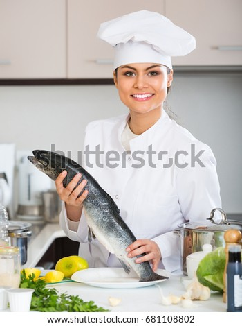 Joyful female chef cooking rainbow trout in commercial kitchen