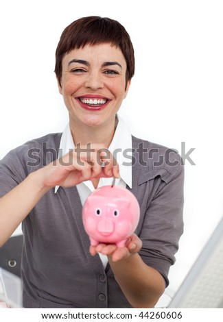 Joyful Female executive saving money in a piggybank isolated on a white background - stock photo