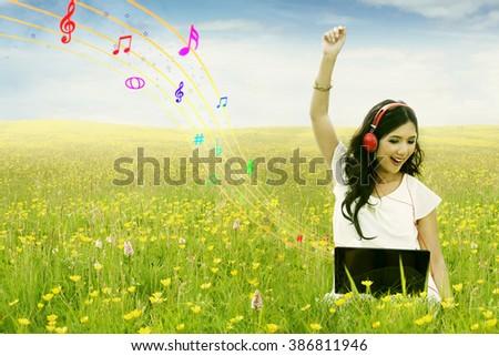Joyful female model sitting on the meadow while listening music with laptop and headphone