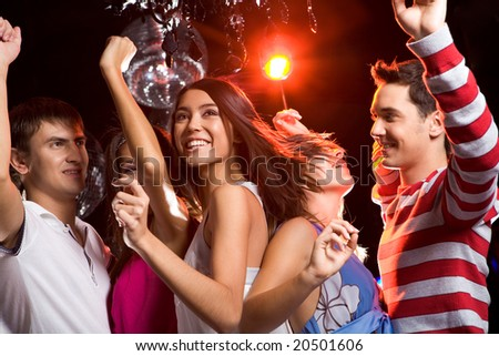 Joyful friends clubbing at discotheque next to each other with smiles