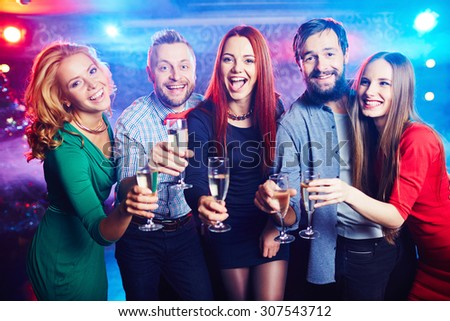 Joyful friends drinking wine at nightclub