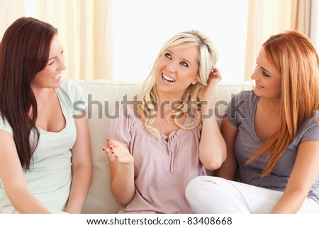 Joyful friends sitting on a sofa in a living room - stock photo