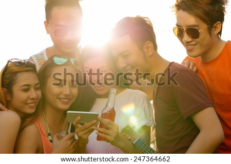 Joyful friends using application on the smartphone