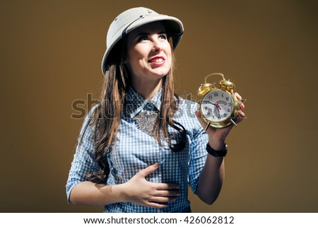 Joyful funny young woman in jeans shirt and pith helmet holding alarm clock over brown background - stock photo