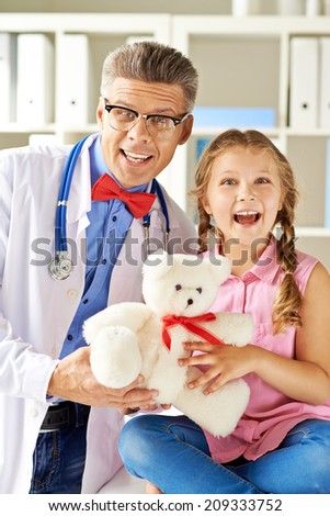 Joyful girl and her doctor looking at camera in hospital - stock photo