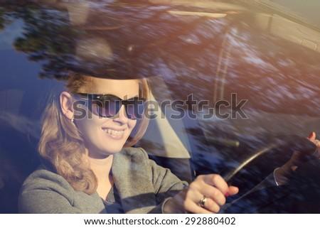 Joyful girl driving a car - stock photo