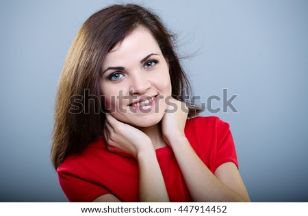 Joyful girl in a red T-shirt with flying hair holds her neck hands on a gray background  - stock photo