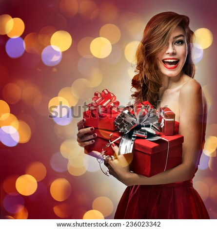 Joyful girl in red dress with gifts - stock photo