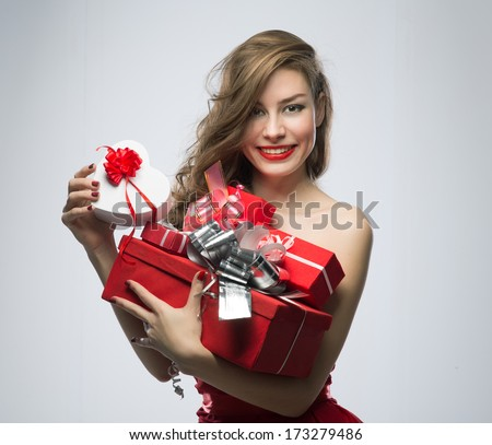 Joyful girl in red dress with gifts on Valentines Day