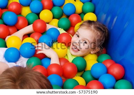 Joyful girl laughing in the pool with colorful balls - stock photo