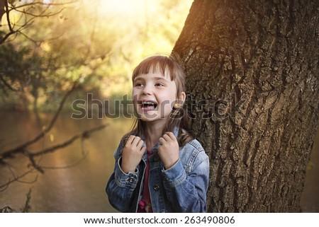Joyful girl laughing in the sunny park - stock photo