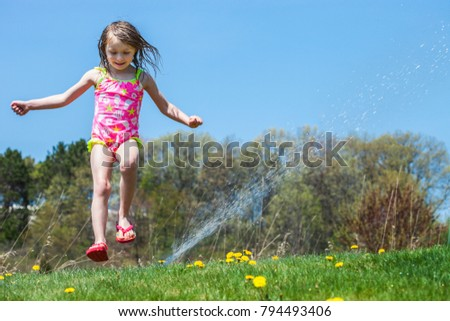 Joyful girl playing with sprinkle water outside and having fun