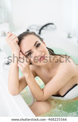 Joyful girl resting in whirlpool bath