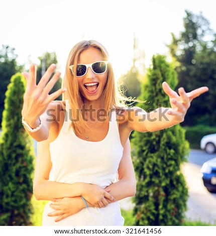 Joyful girl waves her hands, smiling happily with his girlfriend play the fool, pinned summer day having fun enjoying the holiday vacation, summer in the park outdoors. - stock photo