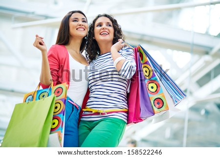Joyful girls with paperbags in trade center - stock photo