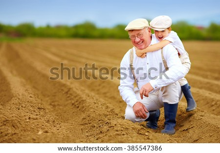 joyful grandpa and grandson having fun on spring plowed field