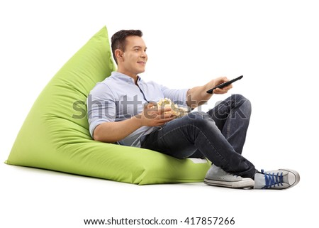 Joyful guy watching TV seated on a green beanbag and eating popcorn isolated on white background - stock photo