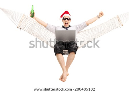 Joyful guy with Santa hat working on a laptop seated in a hammock and drinking beer isolated on white background - stock photo